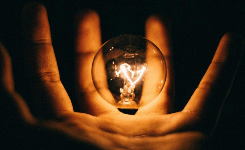 Mano che tiene una lampadina accesa che rappresenta le competenze di una persona per maneggiare la tecnologia
