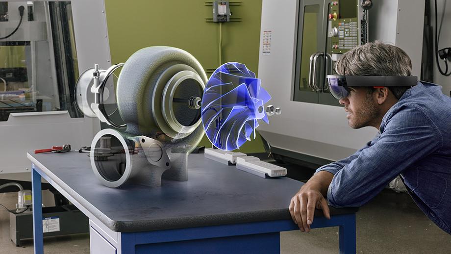 Esempio di mixed reality hololens dove una persona visualizza un modello 3D di una macchina su un ambiente di lavoro